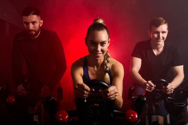 Giovani in abbigliamento sportivo, allenamento in bicicletta in palestra, con l'intenzione dell'assistenza sanitaria. uomini e donne caucasici che cercano di rendere il corpo sano con muscoli tesi e ridurre il peso