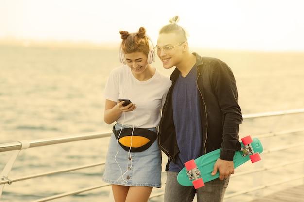 Orario estivo giovanile. elegante coppia hipster innamorata passeggiando sul lungomare e ascoltando musica con le cuffie.