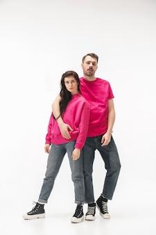 Gioventù. coppia alla moda alla moda isolata su sfondo bianco studio. donna ed uomo caucasici che posano in vestiti alla moda grigi rosa di base. concetto di relazioni, moda, bellezza, amore. copyspace.