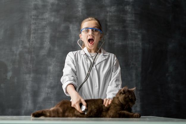 Ragazza giovane con espressione facciale stupita che ti guarda con la bocca aperta mentre esamina il gatto con lo stetoscopio