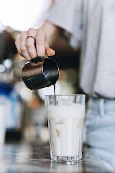 Una giovane bionda piuttosto snella, che indossa un abbigliamento casual, versa il caffè in un bicchiere di latte in un'accogliente caffetteria. .