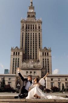 Ypong coppia di sposini, uomo e donna, sposa in abito da sposa, sposo in abito sullo sfondo del paesaggio urbano sono seduti sulla strada con le mani alzate al cielo, felice, giorno del matrimonio.