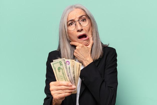 Ysenior pre imprenditrice con banconote in dollari. concetto di denaro