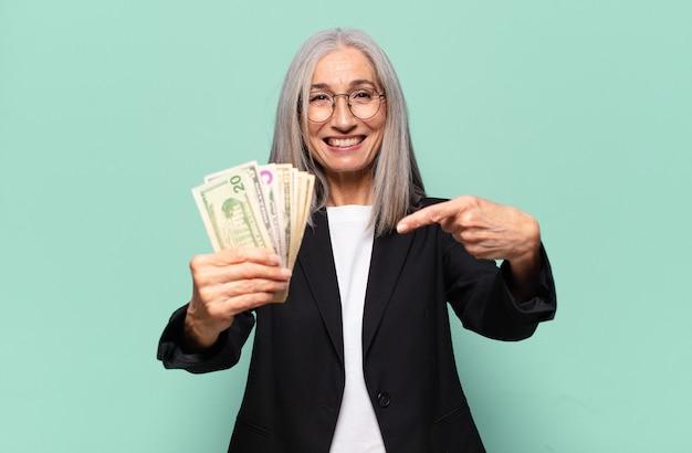Ysenior bella imprenditrice con banconote in dollari.