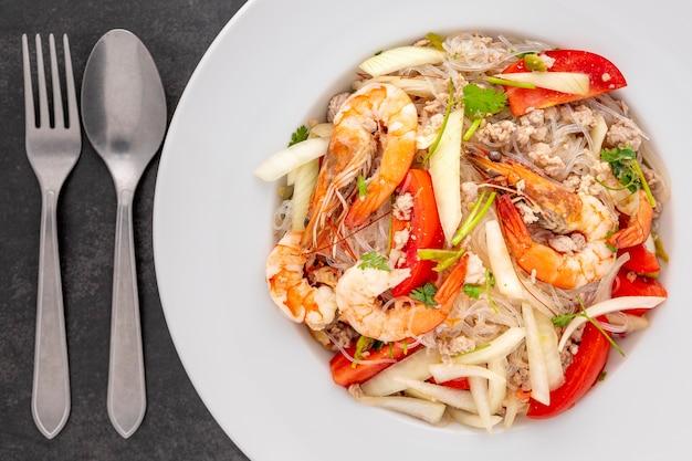Yum woon sen, cibo tailandese, insalata di pasta di vetro tailandese in piatto di ceramica bianca accanto a cucchiaio e forchetta su sfondo texture tono scuro, vista dall'alto