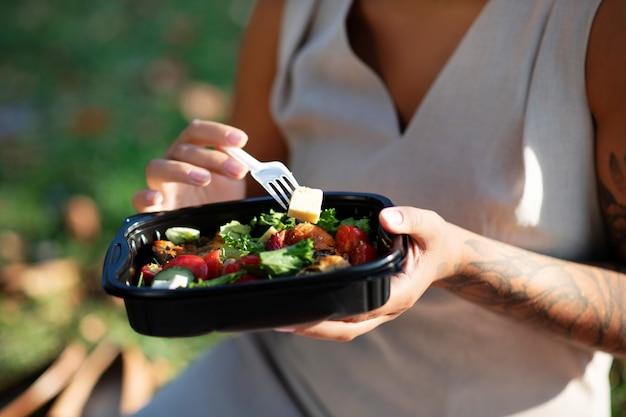 Gustosa insalata sana. chiuda in su della donna tatuata che mangia insalata sana gustosa mentre è seduto nel parco