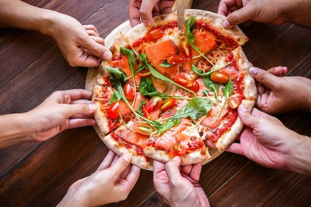 Pizza gustosa con salmone affumicato e verdure su un tavolo di legno, vista dall'alto