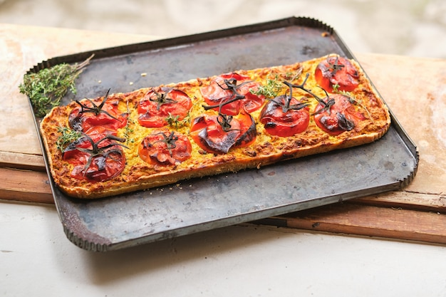 Pizza vegana squisita con pomodori su teglia