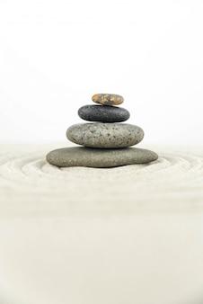 Giardino zen. piramidi di pietre zen bianche e grigie sulla sabbia bianca con disegni a onde astratte.