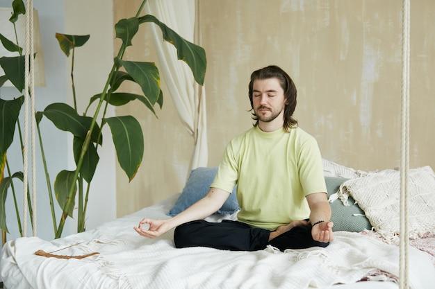 Pratica zen a casa con un bell'insegnante di yoga, fantastico meditatore con i capelli lunghi che pratica la concentrazione a casa