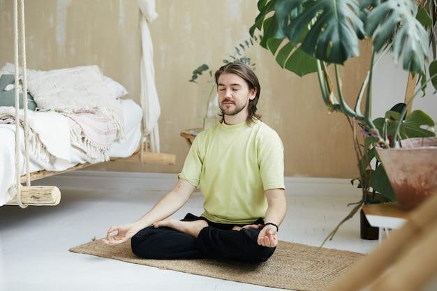 Pratica zen a casa con insegnante di yoga, bel meditatore nella posa del loto e yoga mudra concentrato a casa