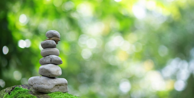 Zen equilibrio in pietra spa all'aperto bellissimo sfondo verde bokeh