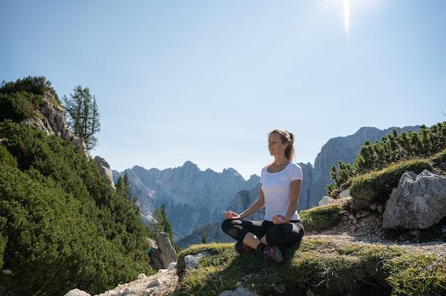 Zen giovane donna seduta nella posizione del loto meditando su una roccia ricoperta di muschio in montagna.