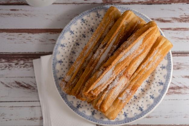 Vista zenitale dei tipici churros ispanici ripieni di dulce de leche in un piatto vintage su vecchie tavole. copia spazio