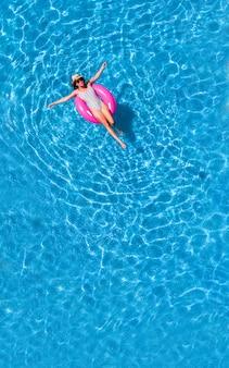 Zenith vista aerea di una piscina in estate. giovane ragazza in costume da bagno e cappello galleggiante con ciambella rosa.