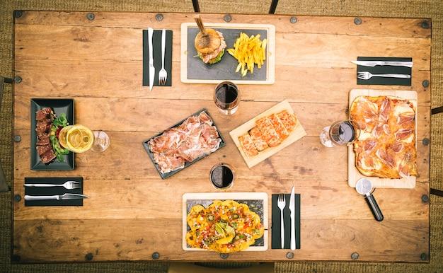 Vista zenith del tavolo rustico con nachos, pizza tradizionale al prosciutto, patatine e hamburger, tataki di tonno e un piatto di prosciutto iberico