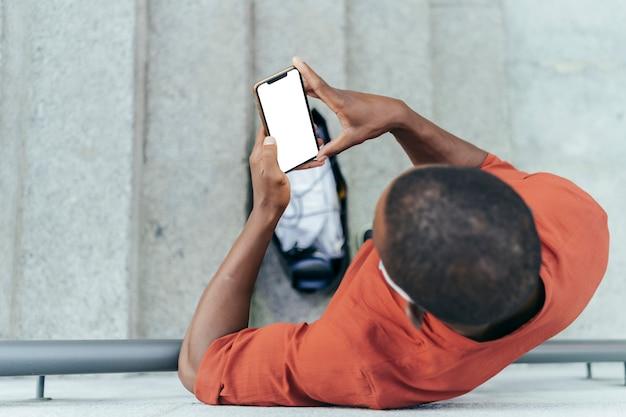 Vista zenitale dell'uomo nero utilizza lo smartphone. sta sostenendo sul muro. indossa una maglietta arancione. è in piedi sulle scale.