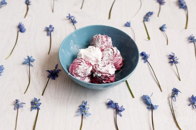 Zefiro. fotografia creativa di cibo. dolci colorati in piatto verde acqua su fiori primaverili