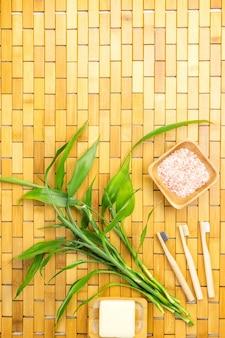Zero concetto vaste con foglie di bambù, portasapone, spazzolini da denti sul tappetino in legno