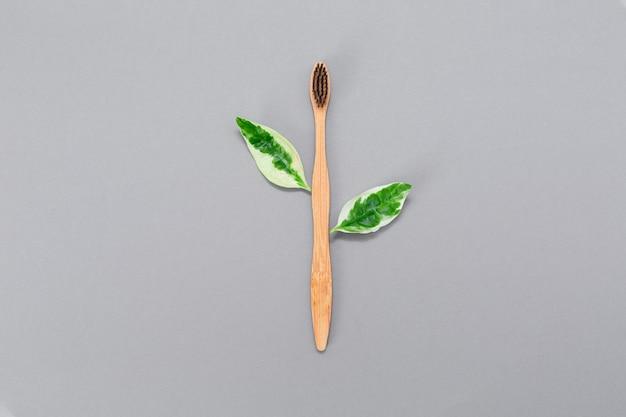 Zero sprechi. spazzolino da denti in bambù con foglie. lay piatto. il concetto di spazzolini ecologici.