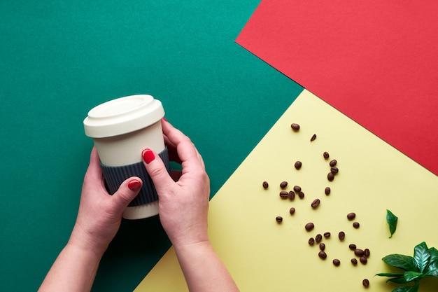 Concetto di caffè a spreco zero. tazze di caffè riutilizzabili ecologiche nelle mani. piatto geometrico disteso su carta bicolore divisa. sfondo creativo in ciano scuro, fiamma rosso scarlatto e colori gialli.