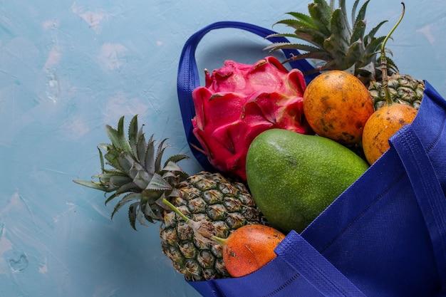 Concetto di rifiuti zero, borsa shopping blu in tessuto con frutti tropicali freschi mango, ananas, drago e frutto della passione