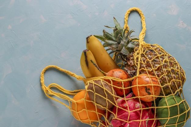 Concetto di rifiuti zero, borsa in tessuto a rete con frutti tropicali freschi mango, ananas, drago, kiwi, banana e frutto della passione