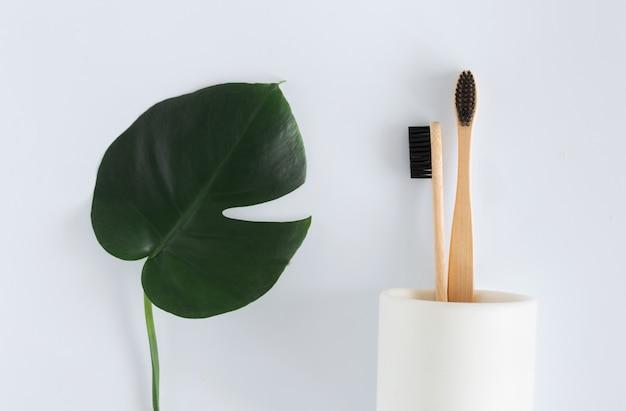 Concetto di rifiuti zero. lo spazzolino da denti di bambù naturale di eco nel supporto con i monstera va sulla vista superiore del fondo bianco copi lo spazio