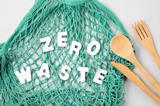Concetto di rifiuti zero. set di posate in bambù ecologico, borsa in cotone a rete, bicchiere da caffè riutilizzabile. shopping sostenibile, etico, stile di vita senza plastica. vista dall'alto, piatto.
