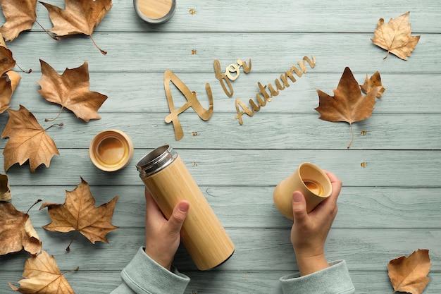 Bevande zero sprechi in autunno. mani che tengono la boccetta di metallo isolata ecologica e la tazza di bambù.