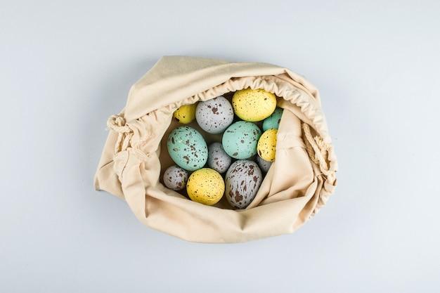 Concetto di pasqua rifiuti zero. uova di pasqua pastelli variopinte nella borsa del tessuto su fondo grigio. vista dall'alto, disteso, copia spazio