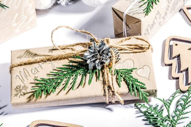Zero sprechi ed eco-friendly concetto di natale piatto con dono, cono e rami di pino su sfondo bianco.