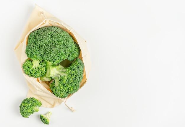 Broccoli crudi di stoccaggio di cibo a spreco zero in borsa eco su superficie bianca