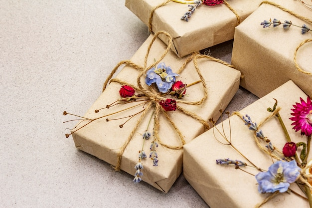 Concetto di regalo zero rifiuti. compleanno confezione ecologica. scatole festive in carta artigianale con diverse decorazioni organiche.