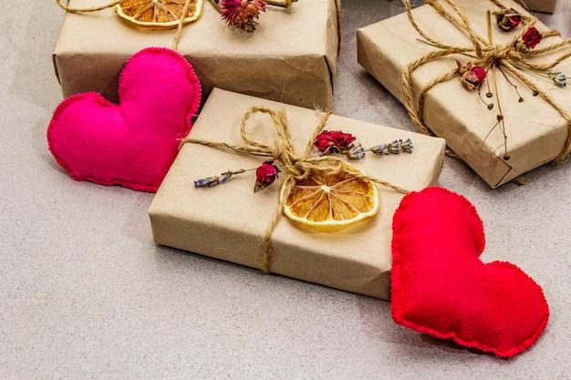 Concetto di regalo zero rifiuti. imballaggio ecologico per san valentino o compleanno. scatole festive in carta artigianale con diverse decorazioni organiche.