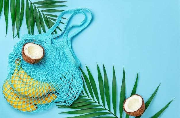 Sacco a rete zero rifiuti con banane e cocco su sfondo blu brillante. direttamente sopra, copia spazio.