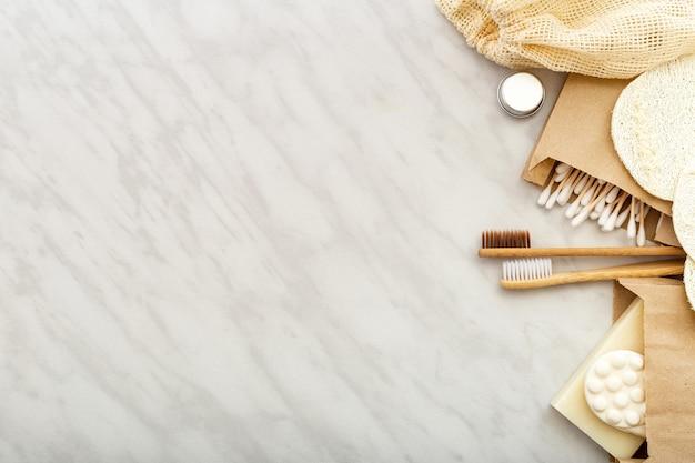 Prodotto da bagno naturale a spreco zero. spazzolini da denti di bambù, bastoncini di legno di tamponi di cotone di sapone, salviette di luffa su fondo di marmo bianco.