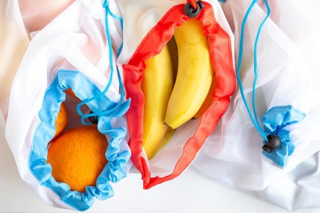 Zero rifiuti, borsa per prodotti tessili in plastica riciclata per il trasporto di frutta (arancia e banana) o verdura, una superficie bianca. vista dall'alto