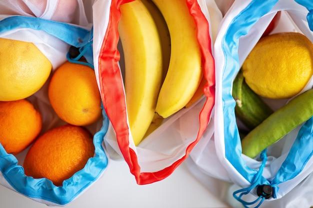Rifiuti zero, borsa per prodotti tessili riciclati in plastica per il trasporto di frutta (arancia, limone, fagioli e banana) o verdura, una superficie bianca. vista dall'alto