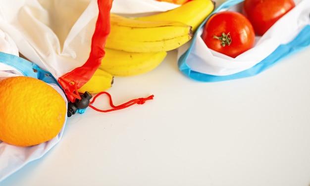 Rifiuti zero, borsa per prodotti tessili in plastica riciclata per il trasporto di frutta (arancia, limone, pomodoro e banana) o verdura, una superficie bianca. vista dall'alto. mockup copyspace