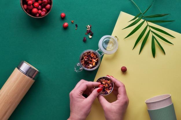 Zero sprechi di tè nella borraccia da viaggio. preparare un'infusione di erbe in una boccetta di bambù isolata ecologica con miscela di erbe e mirtillo rosso fresco. piatto alla moda disteso con le mani, carta bicolore verde e gialla.