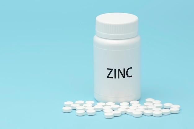 Zinco in confezione bottiglia bianca con pillole sparse.