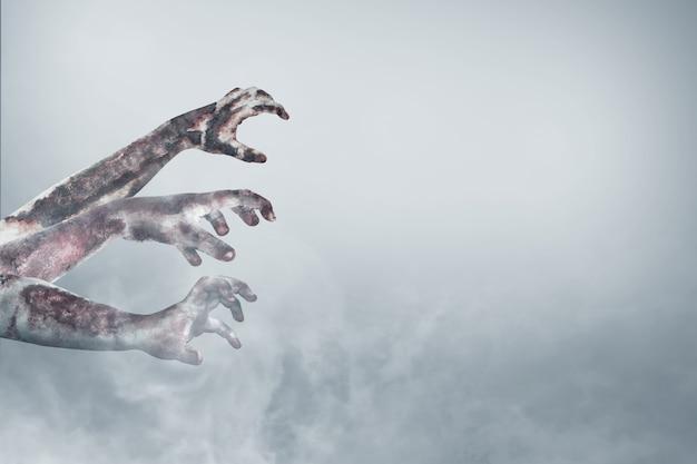 Mano di zombie con sangue e ferita nella nebbia