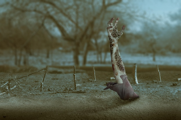Mano di zombi con sangue e ferita sollevata da terra