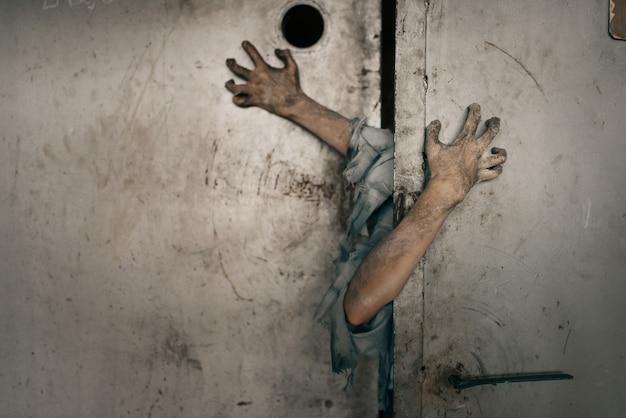 Mani di zombie che spuntano dalla porta dell'ascensore