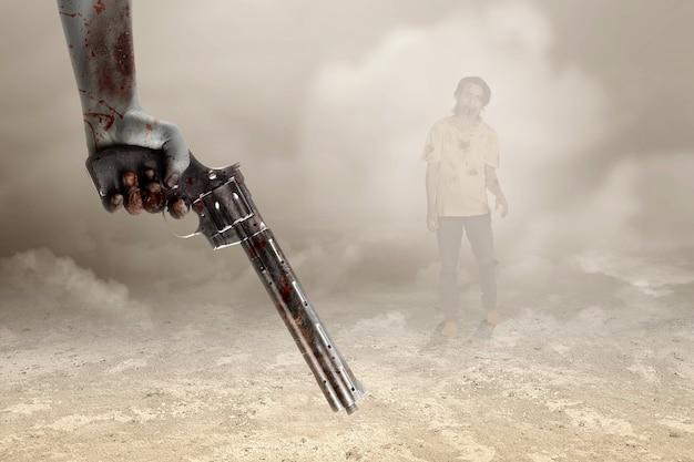 Mani di zombie con ferita che tengono una pistola con sfondo nebbioso