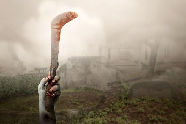 Mani di zombie con ferita che tiene falce con sfondo nebbioso