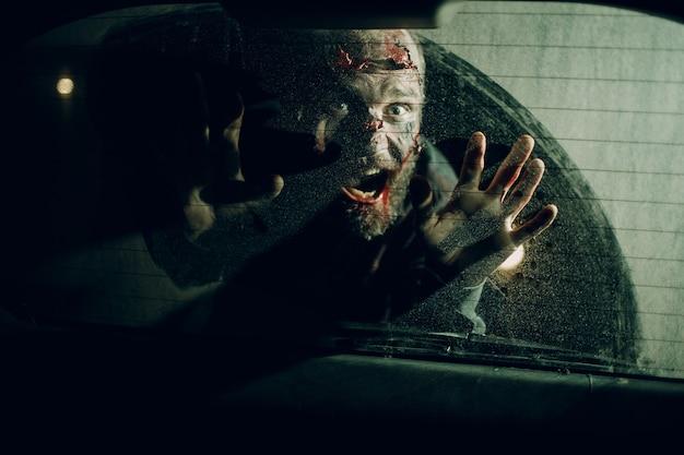 Autista di auto di attacco maschio di zombie attraverso il concetto di halloween di vetro del finestrino del veicolo.