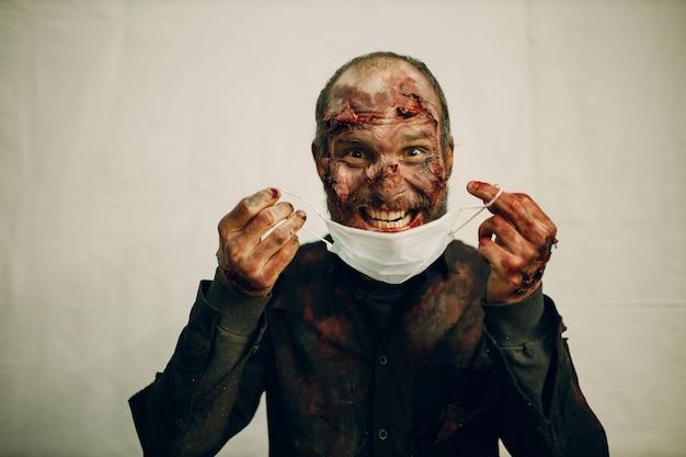 Trucco maschile zombie che indossa una maschera medica che copre il concetto di festa di halloween di protezione.