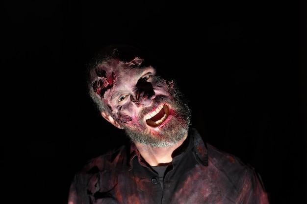 Ritratto di uomo zombie nell'oscurità con il trucco per la festa di halloween
